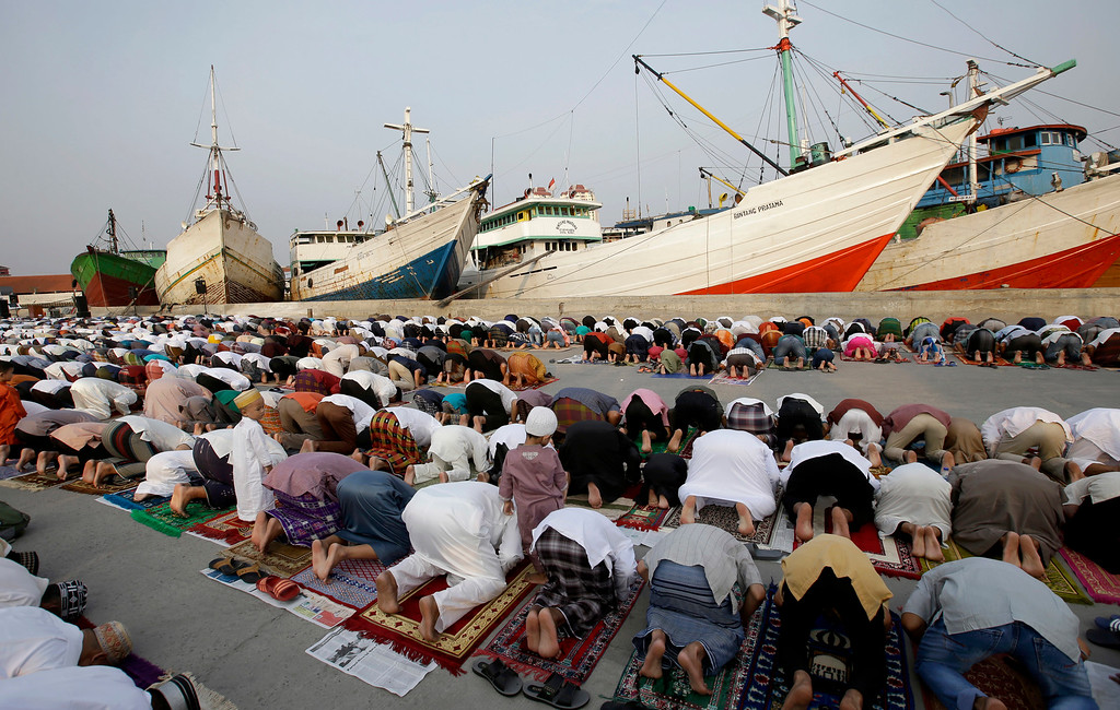 . Indonesian Muslims offer Eid al-Fitr prayers to mark the end of the holy fasting month of Ramadan at Sunda Kelapa port in Jakarta, Indonesia, Friday, June 15, 2018. (AP Photo/Tatan Syuflana)