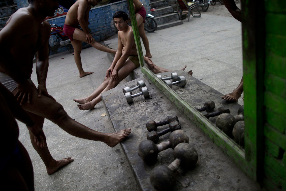 . Pakistani Kushti wrestlers stretch their legs, before training, at a wrestling club in Lahore, Pakistan, Tuesday, Feb. 26, 2013. Kushti, an ancient Indo-Pakistani form of wrestling, is several thousand years old and is a national sport in Pakistan. (AP Photo/Muhammed Muheisen)