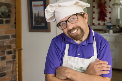 Portrait of a smiling young man with a mustache and beard wearing glasses, a purple shirt, a white chef's hat and white cooks apron with arms crossed, in his home with his kitchen in the background.