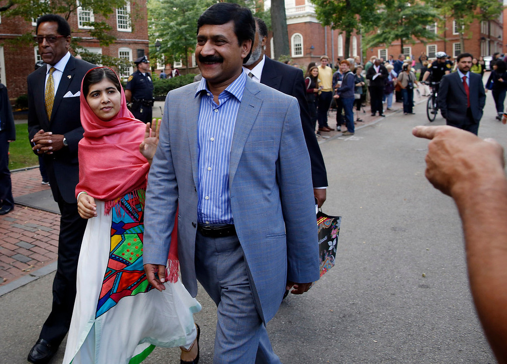 . Malala Yousafzai waves to onlookers as she walks with her father, Ziauddin Yousafzai, right, and Director of the Harvard Foundation and Professor of Neurology at Harvard Medical School Dr. S. Allen Counter, through Harvard Yard after a news conference on the campus in Cambridge, Mass. on Friday, Sept. 27, 2013. The Pakistani teenager, an advocate for education for girls, survived a Taliban assassination attempt in 2012 on her way home from school. (AP Photo/Jessica Rinaldi)