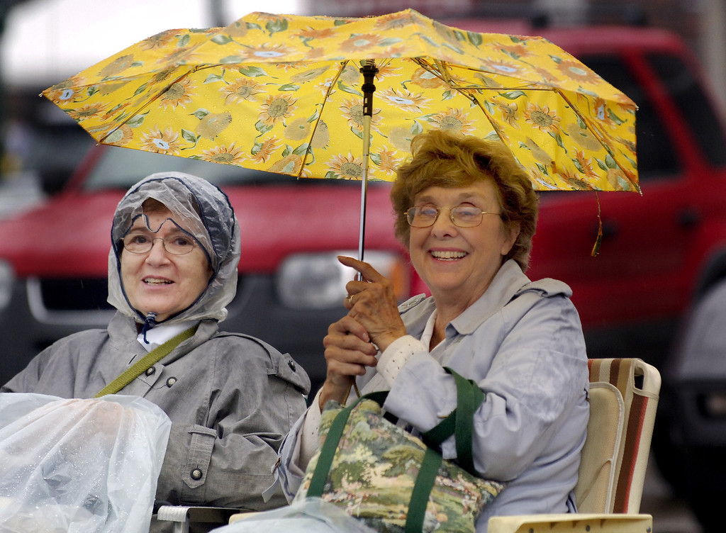 . Katherine Gribbs (left) of Northville and friend Janet Dulmage of Orchard Lake sit in the rain Saturday morning onlong Woodward near 15 Mile Rd. waiting for cruisers to start passing by.