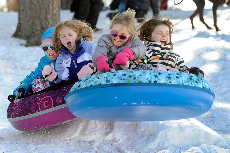 . From left to right, Katie Ingle, 8, Faith Budreau, 5, Stella Ingle, 5, and Elise Myren, 6, vault themselves off a small jump as they join several families gathered at Robinson Park to get in some sledding before the weekend snow begins to melt later in the week with warmer weather forecasted. These Denver families and their kids begin their spring break week today. (Photo By Kathryn Scott Osler/The Denver Post)