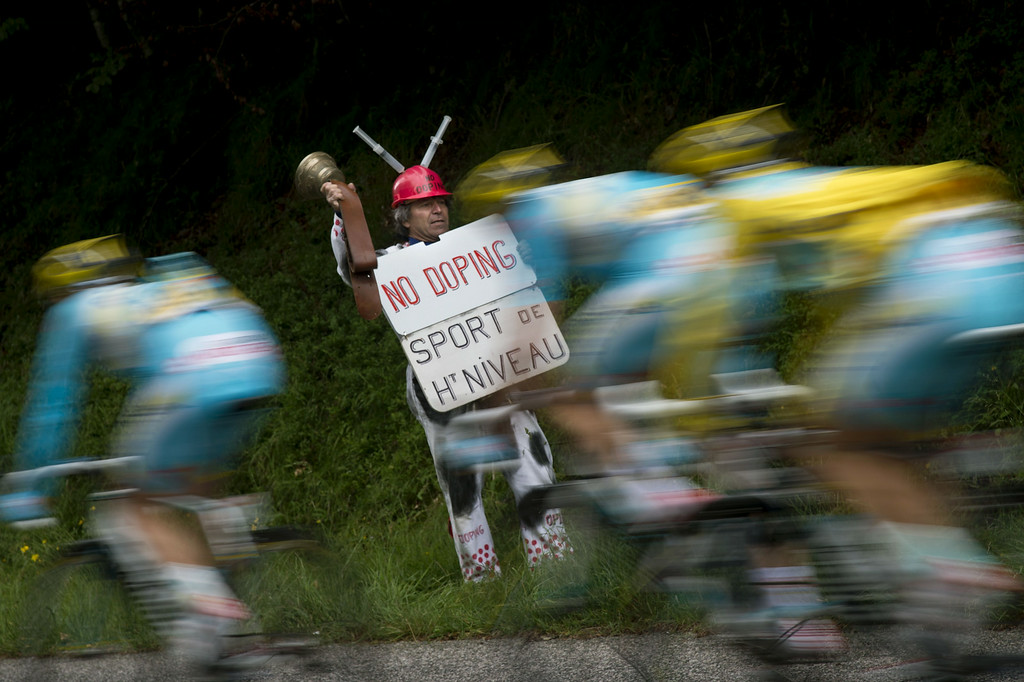 ". A supporter holds a placard reading ""No doping. Top-level sport\"" as Kazakhstan\'s Astana cyclists ride past during the 170 km ninth stage of the 101st edition of the Tour de France cycling race on July 13, 2014 between Gerardmer and Mulhouse, eastern France.  LIONEL BONAVENTURE/AFP/Getty Images"