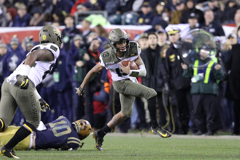 Army quarterback #13 Christian Anderson evades an attempted tackle by Navy#10 Kevin Brennan.