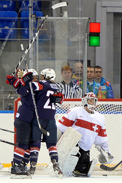. Amanda Kessel (28) of the U.S.A. celebrates her goal with teammate Brianna Decker (14) as Florence Schelling (41) of the Switzerland reacts during the first period of action at the Shayba Arena. Sochi 2014 Winter Olympics on Monday, February 10, 2014. (Photo by AAron Ontiveroz/The Denver Post)