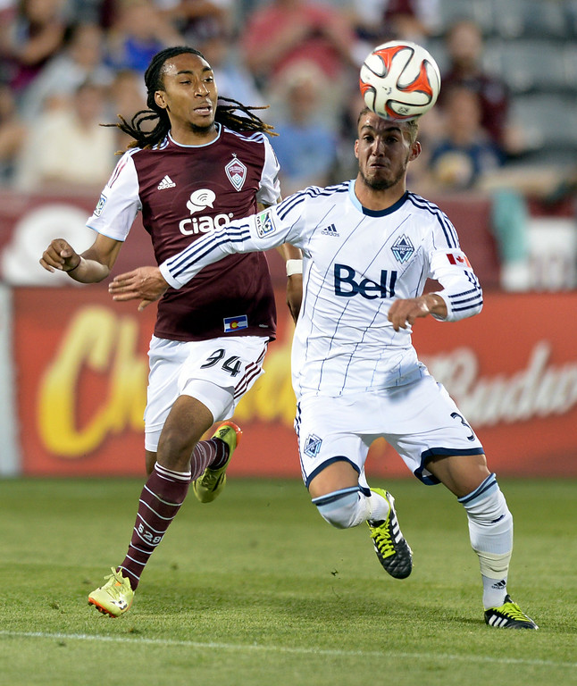 . COMMERCE CITY, CO - JUNE 28: Colorado midfielder Marlon Hairston (94) and Vancouver forward Russell Teibert (31) chased down a ball in the second half. The Colorado Rapids defeated the Vancouver Whitecaps 2-0 at Dick\'s Sporting Goods Park Saturday night, June 28, 2014.  Photo by Karl Gehring/The Denver Post