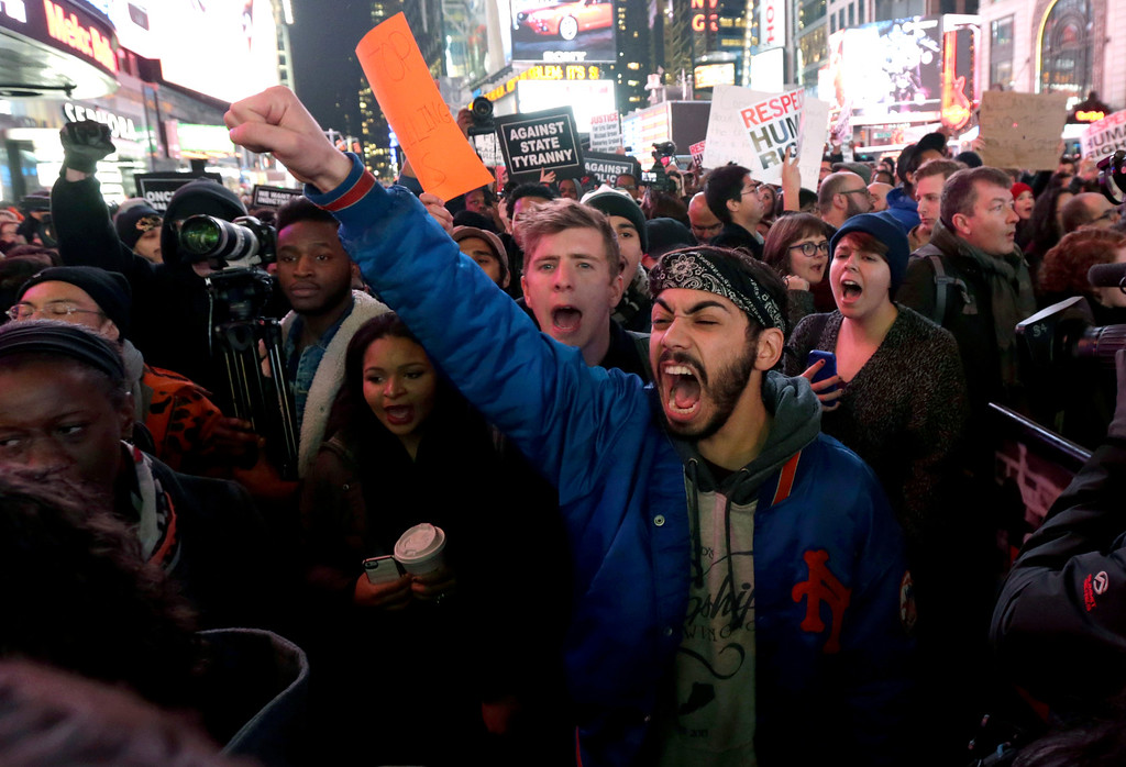 . Protestors shout at Times Square after it was announced that the New York City police officer involved in the death of Eric Garner is not being indicted, Wednesday, Dec. 3, 2014, in New York. A grand jury cleared the white police officer Wednesday, although the city medical examiner ruled Garner\'s death a homicide and found that a chokehold contributed to it. (AP Photo/Julio Cortez)