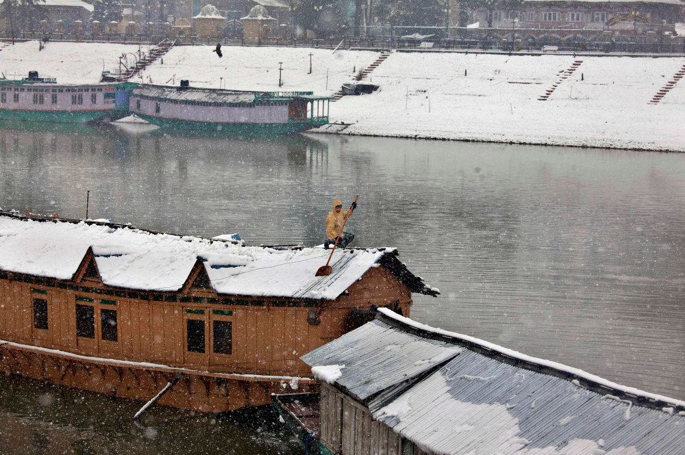 . A Kashmiri Muslim boy clears snow from the roof of his houseboat in Srinagar, India, Friday, Jan. 18, 2013. Traffic on the 300 kilometers (186 miles) long Jammu-Srinagar national highway was suspended due to heavy snowfall, according to news reports. (AP Photo/Dar Yasin)