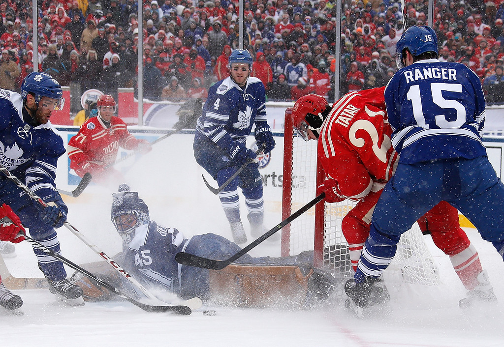 . Tomas Tatar #21 of the Detroit Red Wings moves in front of Paul Ranger #15 of the Toronto Maple Leafs as goalie Jonathan Bernier #45 of the Leafs scrambles to recover during the 2014 Bridgestone NHL Winter Classic at Michigan Stadium on January 1, 2014 in Ann Arbor, Michigan. (Photo by Gregory Shamus/Getty Images)
