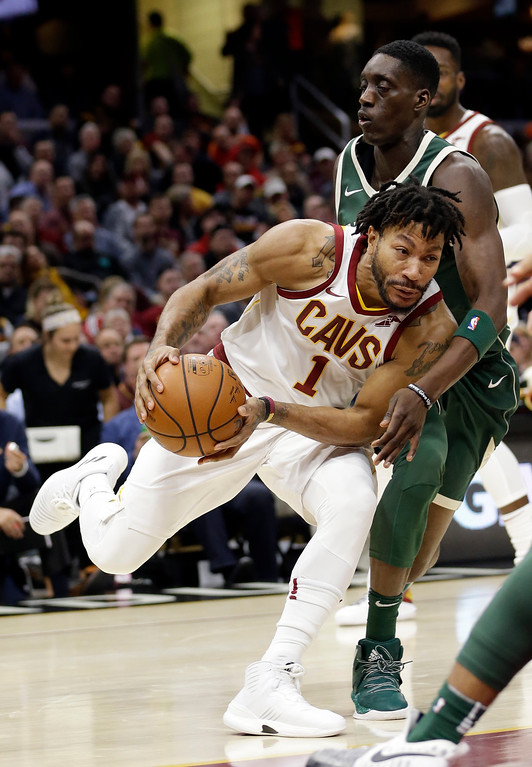. Cleveland Cavaliers\' Derrick Rose (1) drives past Milwaukee Bucks\' Tony Snell (21) in the first half of an NBA basketball game, Tuesday, Nov. 7, 2017, in Cleveland. (AP Photo/Tony Dejak)