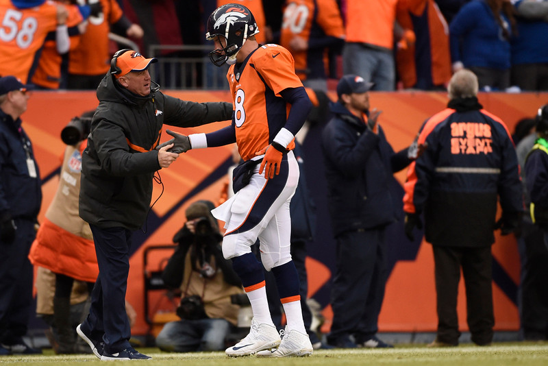 . Peyton Manning (18) of the Denver Broncos is congratulated by head coach John Fox of the Denver Broncos while returning the sidelines after throwing a touchdown pass in the first quarter. The Denver Broncos played the Indianapolis Colts in an AFC divisional playoff game at Sports Authority Field at Mile High in Denver on January 11, 2015. (Photo by AAron Ontiveroz/The Denver Post)
