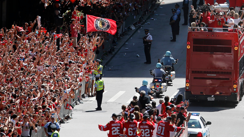 . Chicago Blackhawks\' captain Jonathan Toews (R) holds the Stanley Cup as a bus drives past fans lining the street during the team\'s NHL Stanley Cup parade in Chicago, Illinois, June 28, 2013. REUTERS/Jim Young