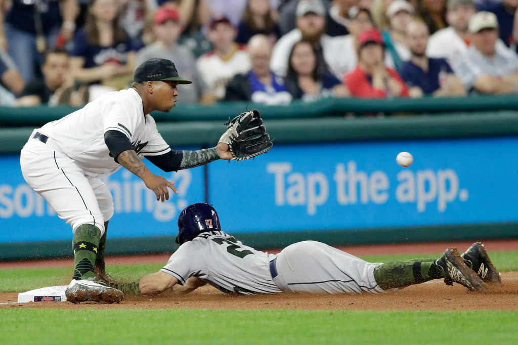 . Houston Astros\' Jose Altuve slides into third base for a triple as Cleveland Indians\' Jose Ramirez waits for the ball in the seventh inning of a baseball game Saturday, May 26, 2018, in Cleveland. (AP Photo/Tony Dejak)
