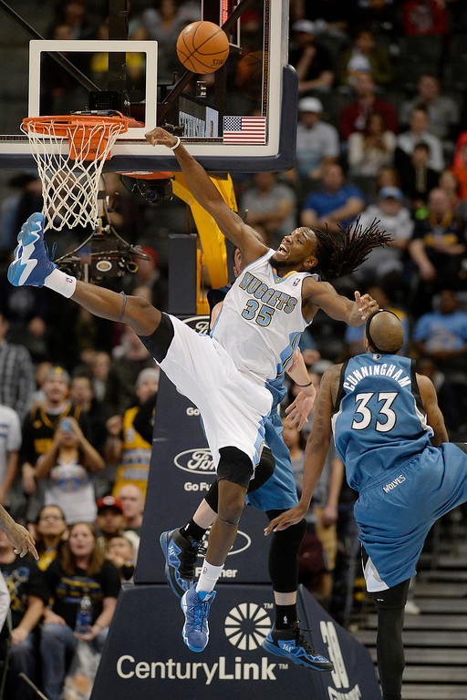 . Dante Cunningham (33) of the Minnesota Timberwolves fouls Kenneth Faried (35) of the Denver Nuggets as Kevin Love (42) of the Minnesota Timberwolves gives help on the defensive effort during the second half. (Photo By AAron Ontiveroz/The Denver Post)