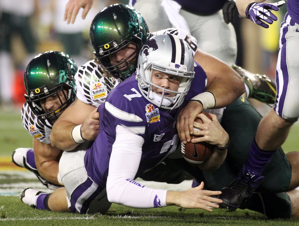 Description of . Kansas State Wildcats quarterback Collin Klein (7) is taken down for a first quarter loss by Oregon Ducks defensive tackle Isaac Remington (C) during the Fiesta Bowl football game in Glendale, Arizona, January 3, 2013. REUTERS/Ralph Freso