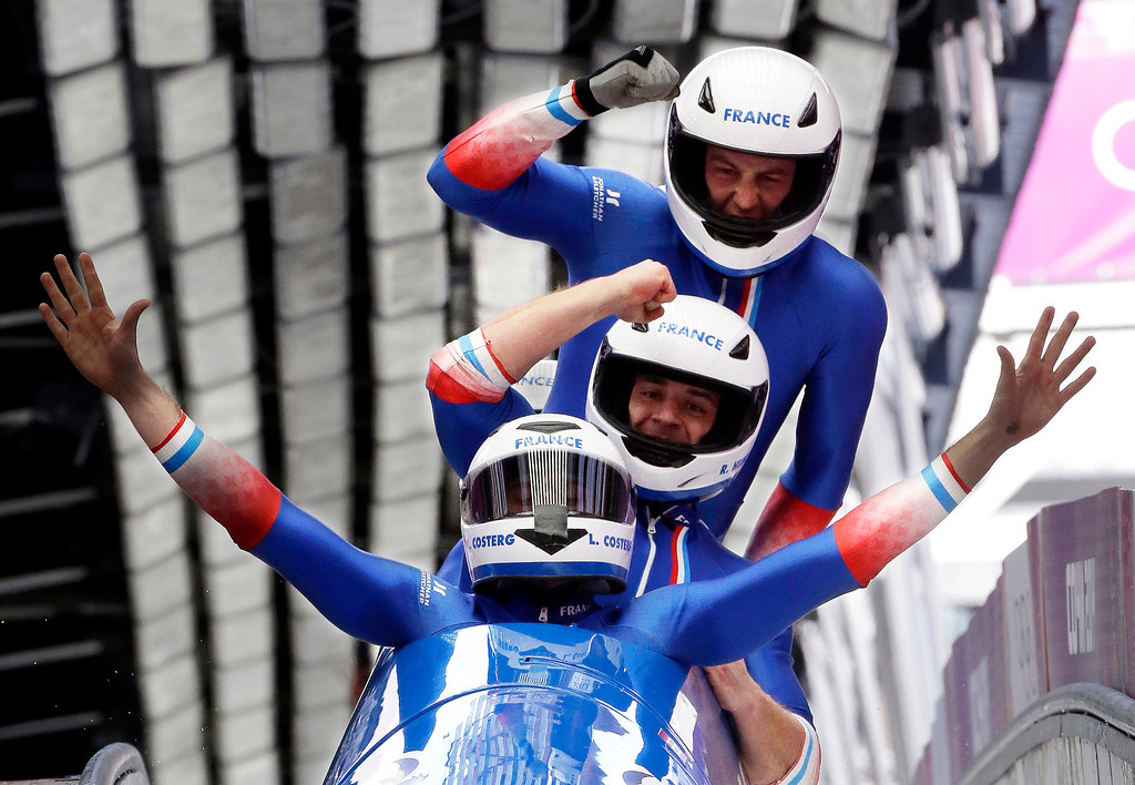 . The team from France FRA-1, with Loic Costerg, Romain Heinrich, Florent Ribet and Elly Lefort, react after their final run during the men\'s four-man bobsled competition final at the 2014 Winter Olympics, Sunday, Feb. 23, 2014, in Krasnaya Polyana, Russia. (AP Photo/Dita Alangkara)