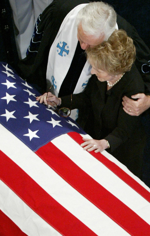. Nancy Reagan(R) is comforted by the Rev. Robert Wenning besides the casket bearing the remains of  her husband former US president Ronald Reagan,  during a private ceremony at the Ronald Reagan Presidential Library in Simi Valley, California, June 7, 2004.  After the private ceremony the remains will be available for public viewing for the next 30 hours before transportation to Washington DC for a state funeral, 11 June at the US Capitol.  (BRYAN CHAN/AFP/Getty Images)