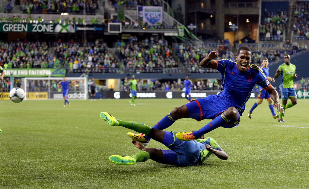 . Colorado Rapids\' Atiba Harris, right, goes down on a slide tackle by Seattle Sounders\' Jhon Kennedy Hurtado in the first half of a knockout-round match in the MLS Cup soccer playoffs, Wednesday, Oct. 30, 2013, in Seattle. (AP Photo/Ted S. Warren)