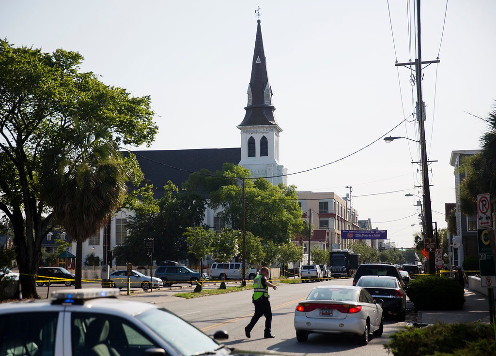 . The steeple of Emanuel AME Church rises above the street as a police officer tells a car to move as the area is closed off following Wednesday\'s shooting, Thursday, June 18, 2015 in Charleston, S.C. (AP Photo/David Goldman)