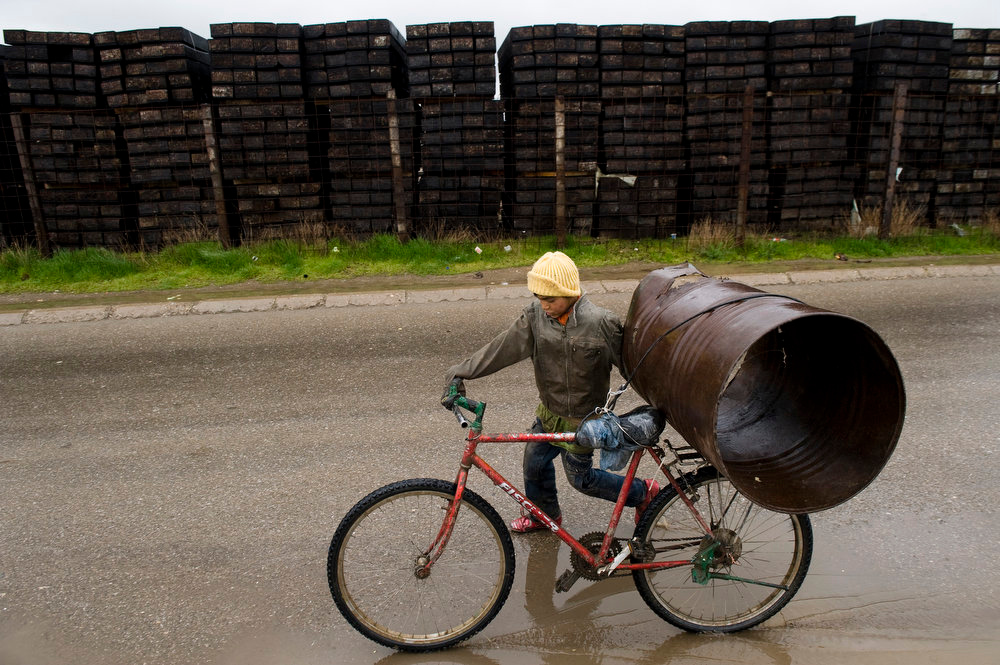 . A Roma child loads recycled items on his bicycle during the International Roma Day in Pristina on April 8, 2013.      AFP PHOTO / ARMEND NIMANI