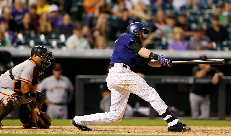 . Colorado Rockies\' Charlie Blackmon, right, follows the flight of his walkoff, RBI-single as San Francisco Giants catcher Guillermo Quiroz looks on in the ninth inning of the Rockies\' 10-9 victory in a baseball game in Denver on Monday, Sept. 1, 2014. (AP Photo/David Zalubowski)