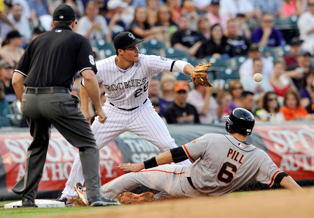 . San Francisco Giants\' Brett Pill (6) steals third as Colorado Rockies third baseman Nolan Arenado covers during the second inning of a baseball game on Friday, May 17, 2013, in Denver. (AP Photo/Jack Dempsey)