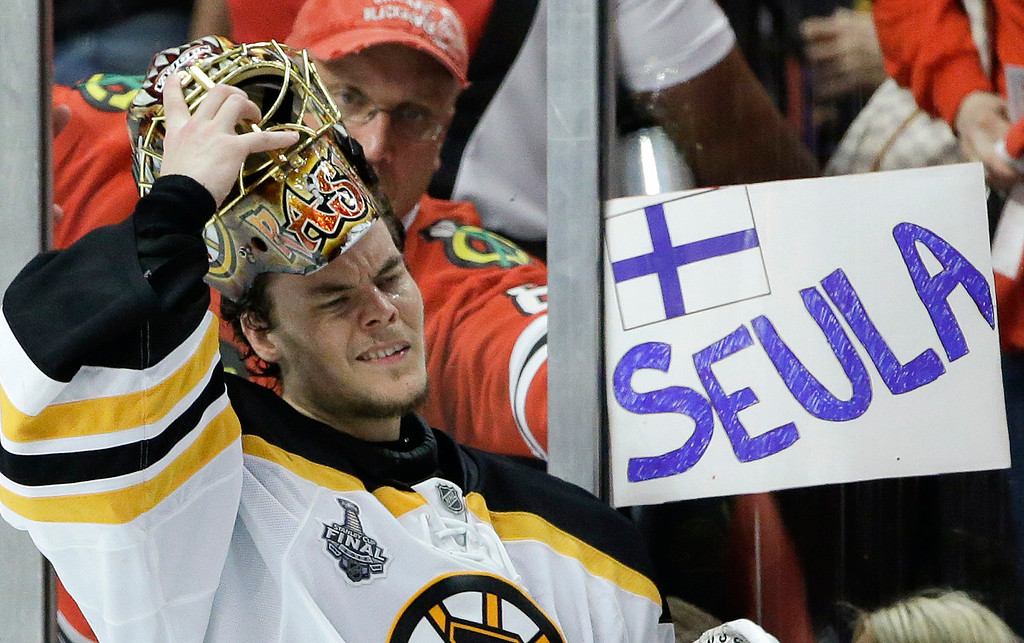 . Boston Bruins goalie Tuukka Rask (40) puts his mask back on after a break in the third period against the Chicago Blackhawks as a fan holds up a sign in Finnish calling Rask a hockey sieve in English, during Game 5 of the NHL hockey Stanley Cup Finals, Saturday, June 22, 2013, in Chicago. (AP Photo/Nam Y. Huh)