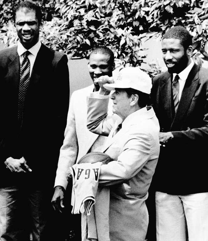 . President Reagan tries on a cap presented to him by members of the Los Angeles Lakers during a ceremony in the White House Rose Garden in Washington on June 10, 1985. From left to right are, Kareem Abdul-Jabbar, Byron Scott, Reagan and James Worthy.(AP Photo)
