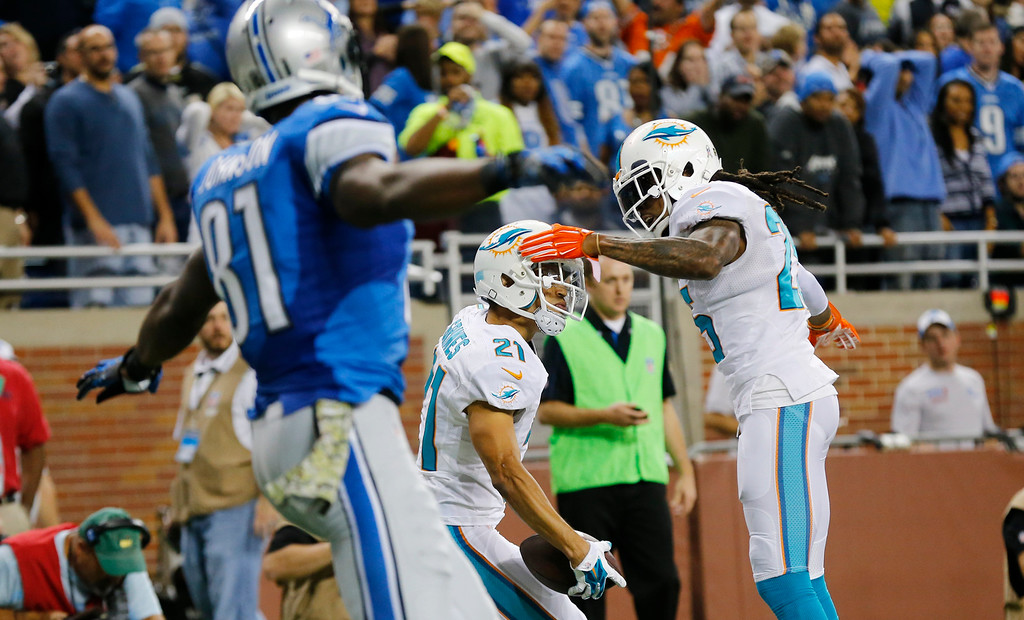 . Miami Dolphins cornerback Brent Grimes (21) celebrates with teammate Miami Dolphins free safety Louis Delmas (25) after intercepting a pass intended for Detroit Lions wide receiver Calvin Johnson, left, during the first half of an NFL football game in Detroit, Sunday, Nov. 9, 2014. (AP Photo/Paul Sancya)