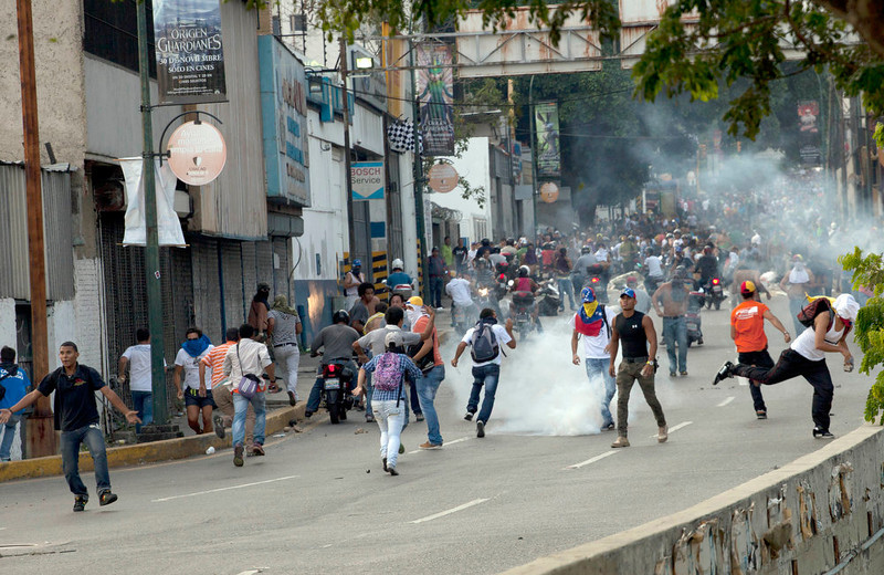 . Opposition supporters and students clash with national guard soldiers and riot police firing tear gas as they protest near a highway in the Altamira neighborhood of Caracas, Venezuela, Monday, April 15, 2013.  National Guard troops dispersed students protesting the official results of Venezuela\'s disputed presidential election. Opposition candidate Henrique Capriles has challenged his narrow loss to Nicolas Maduro and is demanding a recount. (AP Photo/Ramon Espinosa)