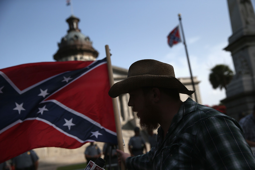 . A Confederate flag supporter stands outside the South Carolina statehouse as the Confederate flag flies on July 9, 2015 in Columbia, South Carolina. South Carolina Governor Nikki Haley signed a bill to remove the Confederate flag from the statehouse grounds Friday morning. (Photo by John Moore/Getty Images)