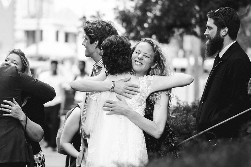 A woman making a funny, smiling face as she hugs the bride on the steps of the church.