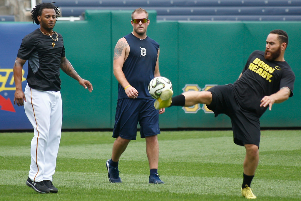 . CORRECTS ID TO IAN KROL, NTO IAN KINSLER - Pittsburgh Pirates\' Russell Martin, right, and Michael Martinez, left, kick a soccer ball around with Detroit Tigers\' Ian Krol, before batting practice for their baseball game on Tuesday, Aug. 12, 2014, in Pittsburgh. (AP Photo/Keith Srakocic)