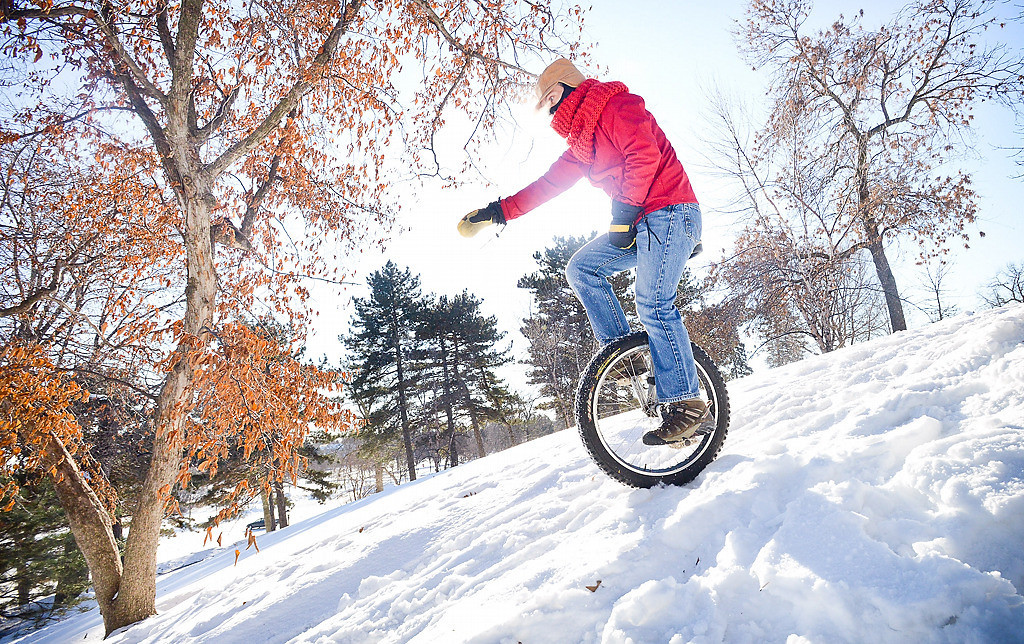 """. Garrett Macey of St. Paul carefully pedals down a steep hill in Como Park on Sunday, Jan. 5, 2014, as members of the Twin Cities Unicycle Club were taking a break from riding around the lake to practice their downhill unicycling skills. \""""It\'s Minnesota, you can\'t let the weather stop you from having a good time,\"""" said Macey. \""""We like to go out and play.\"""" (Pioneer Press: Ben Garvin)"""