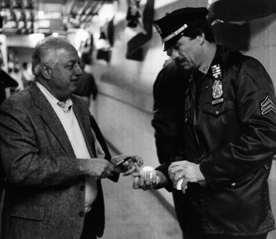 . Los Angeles Dodgers manager Tommy Lasorda signs a baseball for a New York City policeman after arriving at Shea Stadium in New York on Friday, Oct. 7, 1988 for the third playoff game with the New York Mets. (AP Photo/Ray Stubblebine)