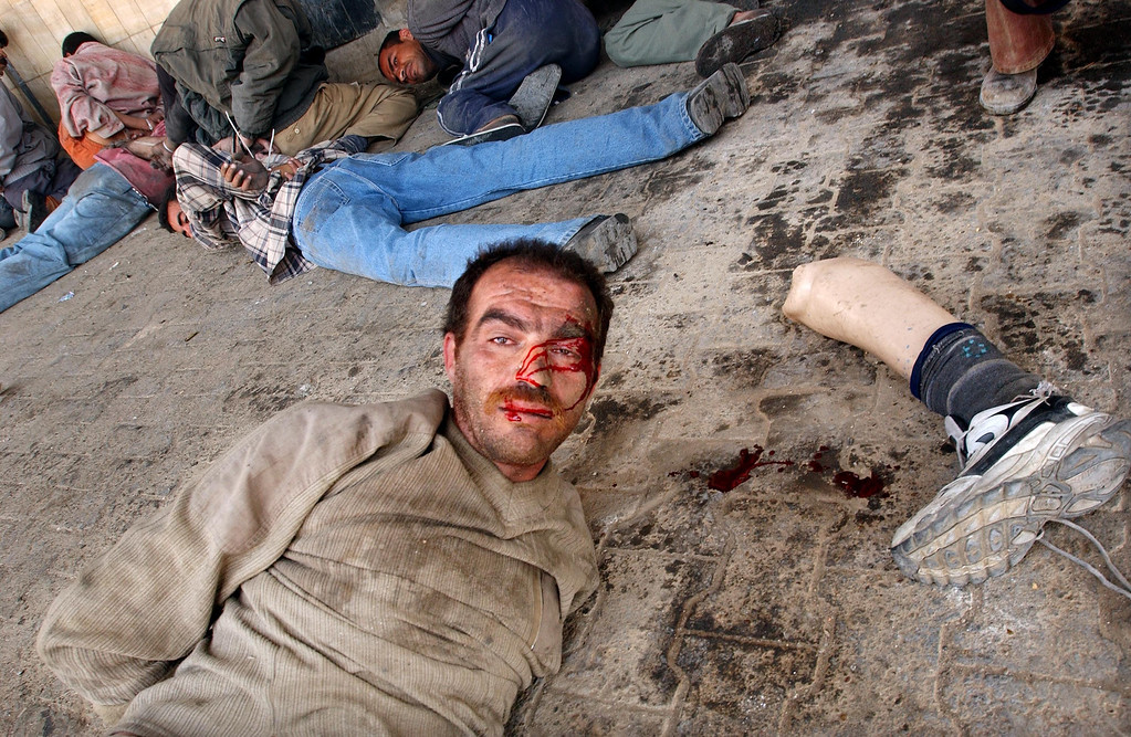 . A man lies handcuffed with his artificial leg near his head after U.S. Marines caught him and other looters robbing from a bank April 16, 2003 in Baghdad, Iraq. (Photo by Spencer Platt/Getty Images)