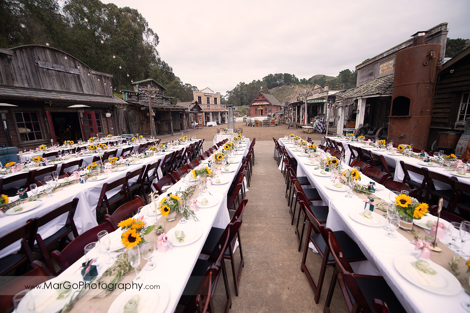 outdoor wedding reception setup with long tables decorated with yellow flowers at Long Branch Saloon & Farms in Half Moon Bay