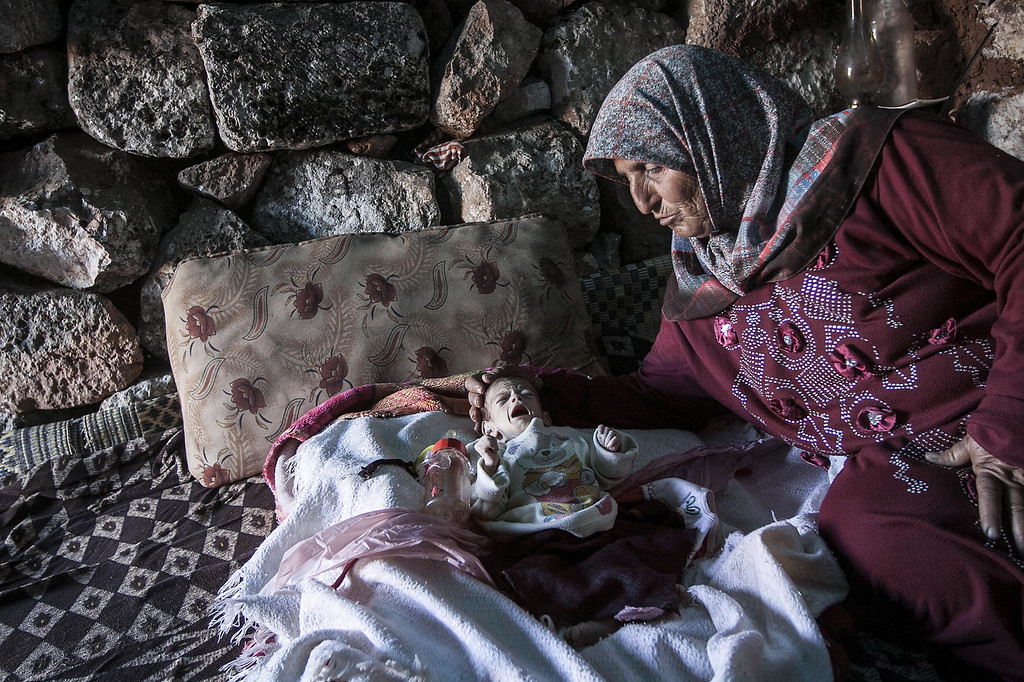 . In this Friday, Sept. 27, 2013 photo, a displaced Syrian woman comforts her one-month old grandchild Fatima inside a stone house near Kafer Rouma, in ancient ruins used as temporary shelter by those families who have fled from the heavy fighting and shelling in the Idlib province countryside of Syria. Fatima was born just a month ago amid the ancient ruins outside Kafer Rouma, a village in northern Syria that has come under shelling by President Bashar Assadís forces during the countryís civil war. Her family fled their home in the village to the giant stone blocks and centuries-old walls so that Fatimaís mother could give birth in relative safety.(AP Photo)