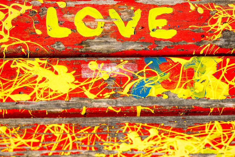"A crazily painted bench in yellow and red with ""love"" painted on it, which has been deteriorating away."