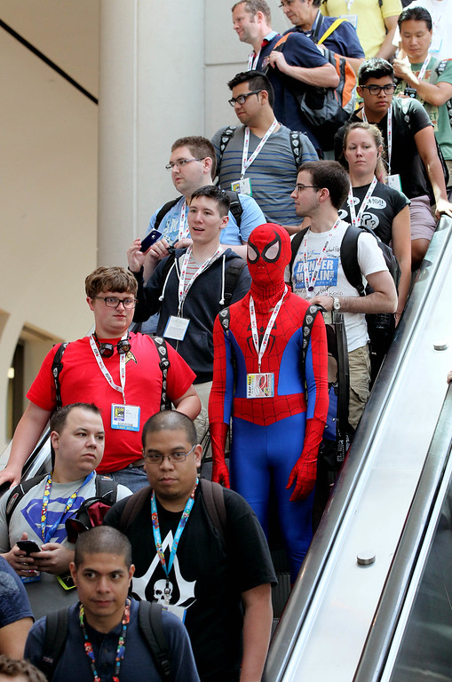 . In this Thursday, July 18, 2013 photo, attendees, including one dressed as Spider-Man, ride down an escalator at  Comic-Con, in San Diego. (AP Photo/U-T San Diego, Charlie Neuman)