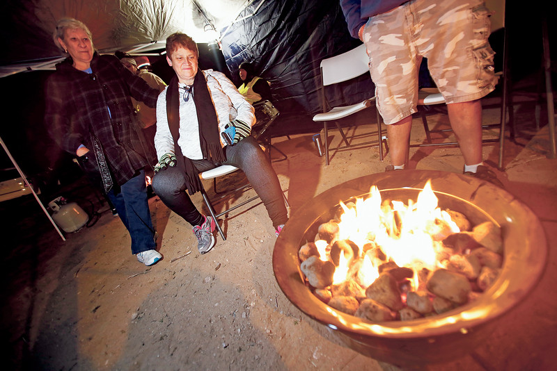 """Frances Lucero, of Santa Fe, and her sister Christine Coriz, take a break by the fire at the Knights of Columbus Tent Prince of Peace tent on their pilgrimage to the Santuario de Chimayo on Good Friday, April 19, 2019. This is Coriz's 10th year walking since she had her knees replaced. """"I walked it again the same year I got my knees replaced,"""" she said. The pair started their pilgrimage from Nambe. Luis Sánchez Saturno/The New Mexican"""