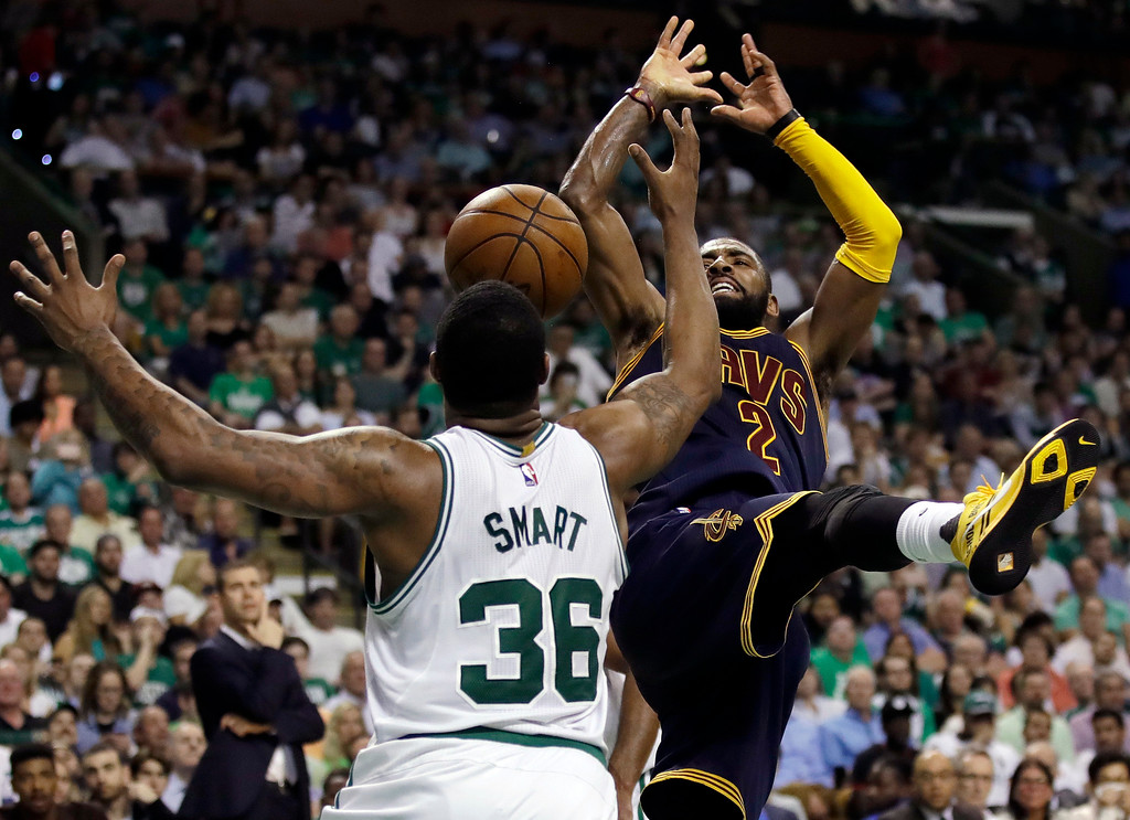 . Cleveland Cavaliers guard Kyrie Irving (2) and Boston Celtics guard Marcus Smart (36) vie for a loose ball during the third quarter of Game 1 of the NBA basketball Eastern Conference finals, Wednesday, May 17, 2017, in Boston. (AP Photo/Charles Krupa)