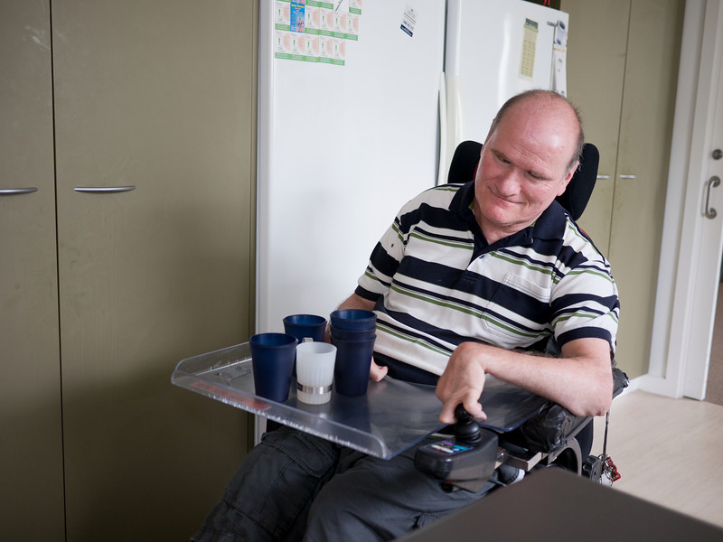 This man, with a disability, is occupied in setting the table at his home.  He has cups on his wheelchair tray and is in transit towards the dining table.