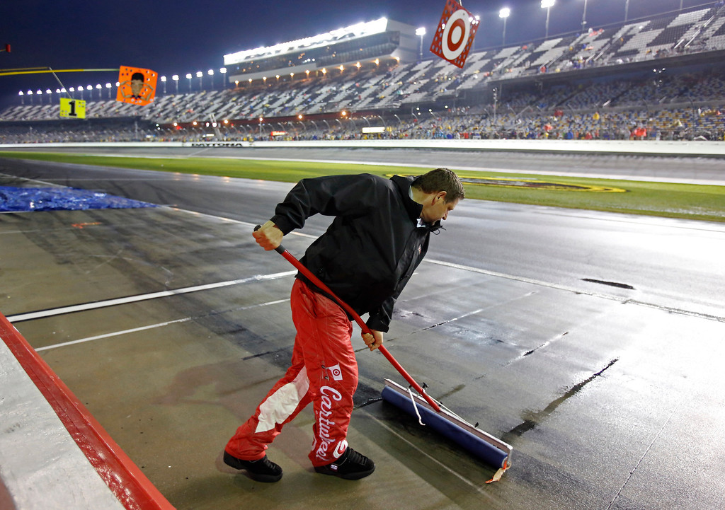 . A crew member uses a squeegee to remove water from pit road during a rain delay in the NASCAR Daytona 500 Sprint Cup series auto race at Daytona International Speedway in Daytona Beach, Fla., Sunday, Feb. 23, 2014. (AP Photo/Terry Renna)