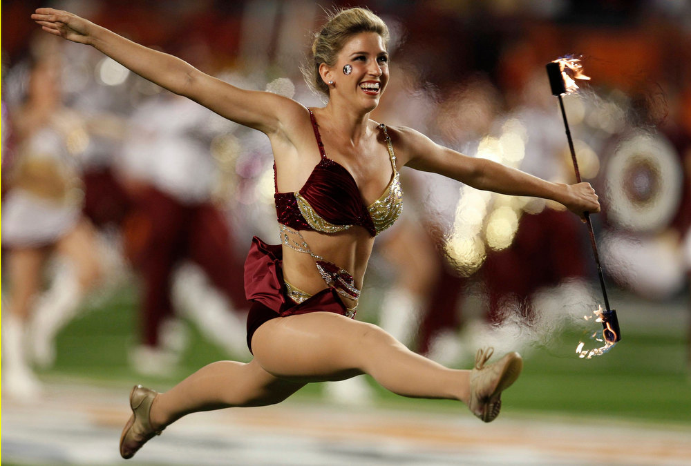 Description of . A Florida State Seminoles baton team member holds a flaming baton as she performs before her team plays against the Northern Illinois Huskies in the 2013 Discover Orange Bowl NCAA football game in Miami, Florida January 1, 2013. REUTERS/Jeff Haynes
