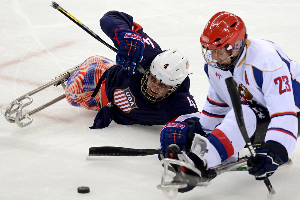 . US Brody Roybal (L) vies with Russia\'s Ilia Volkov during the ice sledge hockey match Russia vs USA during the XI Paralympic Olympic games at the Shayba stadium, near Sochi on March 11, 2014. AFP PHOTO / KIRILL KUDRYAVTSEVKIRILL