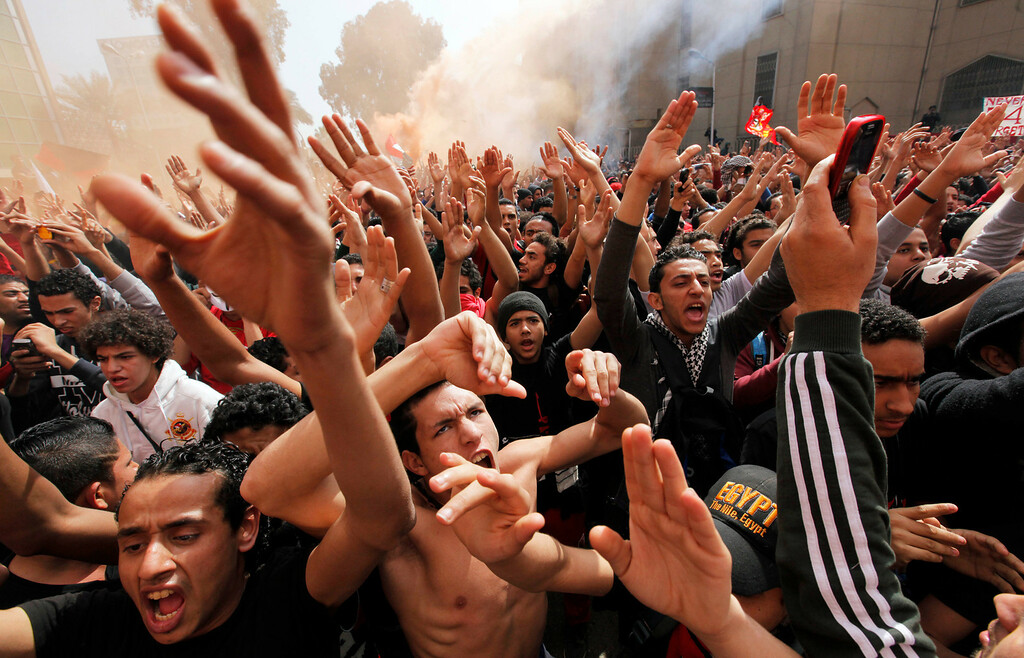 . Egyptian soccer fans of Al-Ahly club celebrate in front of their club headquarters in Cairo, Egypt, Saturday, March 9, 2013. An Egyptian court confirmed death sentences against 21 people for their role in a deadly 2012 soccer riot that killed more than 70 people in the city of Port Said. (AP Photo/Amr Nabil)