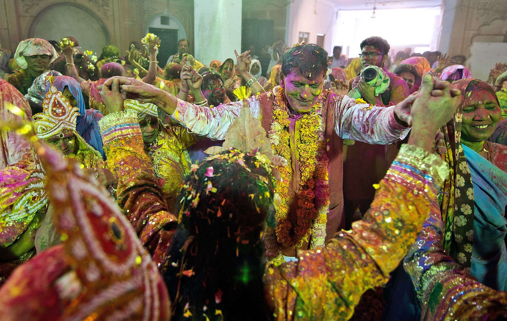 . Indian widows dressed as Hindu god Lord Krishna and Radha dance with Sulabh International founder Bindeshwari Pathak (2nd R) during Holi celebrations in Vrindavan on March 14, 2014.  AFP PHOTO/Prakash SINGH/AFP/Getty Images