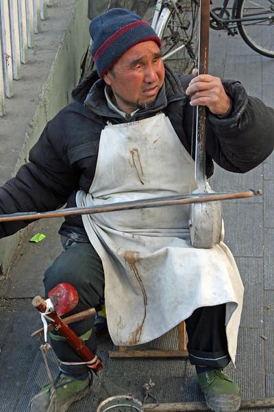Blind Man playing Erhu 2 stringed instrument.Beijing © Lewis Sandler BeijingVideoStudio