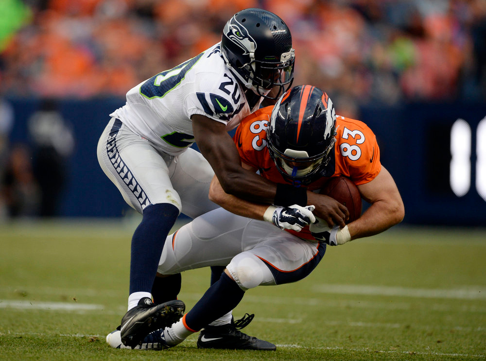 . Wide receiver Wes Welker (83) of the Denver Broncos gets taken down by cornerback Jeremy Lane (20) of the Seattle Seahawks during the first quarter.  The Denver Broncos vs the Seattle Seahawks At Sports Authority Field at Mile High. (Photo by AAron Ontiveroz/The Denver Post)